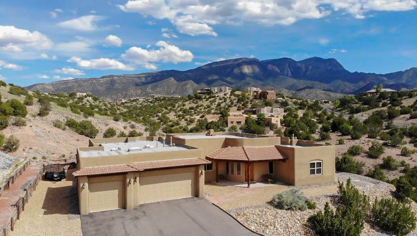 Thoughtfully placed on a 2.71 acre view lot in Placitas' Homesteads subdivision, this incredible single level custom property showcases the amazing views of the Sandia Mountains. Meticulous attention to detail is evident throughout this home! The great room encompasses the kitchen/dining/living areas with custom plaster kiva fireplace, raised ceilings, and access to the expansive covered patio. The spacious kitchen features custom cabinetry, expansive granite counters, a breakfast bar, S/S Jenn Air appliances and large pantry. The separate master suite with his-and-hers en-suite spa-like bath - with 12'x17' walk in closet! - is a welcoming retreat. Amenities include: radiant heat, 2 heat/refrig air units, 75 gal water heater, RV parking, oversized garage, hot tub & more! Cable & Nat gas!