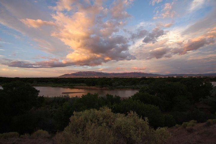 Situated in the Vista Magnifica Subdivision this home offers Stunning City, Mountain and Bosque views.   House Features 4 bedrooms with private bathrooms and walk-in closets creating opportunity for a Vacation Rental or AirBNB or entertaining clients. Kitchen is equipped with stainless steel appliances, maple cabinets, crown molding accents, recessed lights, sky lights, spacious laundry room. Spanish Style roof, energy efficient windows, 189/sf sunroom, synthetic stucco and welcoming water feature in the front yard.  Paved Side Yard access to back yard & house plus extended driveway with carport for more creative options.  Gorgeous private deck off master suite with the some of the best views of the City!  Minutes away from bike path, Downtown, Old Town, UNM and hospita