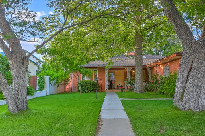 One of a Kind in the Spruce Park Historical District! This fantastic brick home has a streetscape of beautiful trees, green grass, lush landscaping and within walking distance of UNM and University Hospital.Corian countertops, Maple cabinets and woodburning fireplace! 3 bedrooms plus office. Huge Master Suite on privacy sideopposite of the oversized bedrooms. Alarm system, ceiling fans and track lighting. Huge Sunken Living Room. Newer vinyl windows throughout and just installed asphalt shingle roof and gutters in May of 2019'.