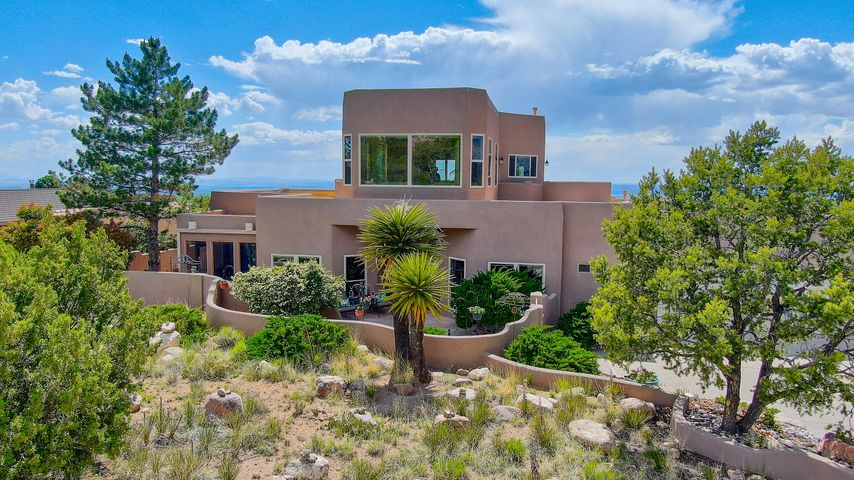 ROBUST REVIVAL in this custom contemporary southwest style home. 360 panoramic vistas- seems like the top of the mountain! Exceptional east/west mountain to city views and beyond. Sandia Heights living with best views and natural light. Outstanding major remodels by Poulin and Jade make this an amazing showplace and first on your list! The chef's kitchen of your dreams combined with the tremendous master suite that won't allow you leave- be captivated! Main level master includes enormous walk-in, sitting area, own private enclosed mountain view patio and even a sauna in the spa-like bath. Multiple living and dining areas, large bedrooms, loft, two custom gas fireplaces and an open plan that facilitates huge functionality. Don't wait, call now to see this home today!