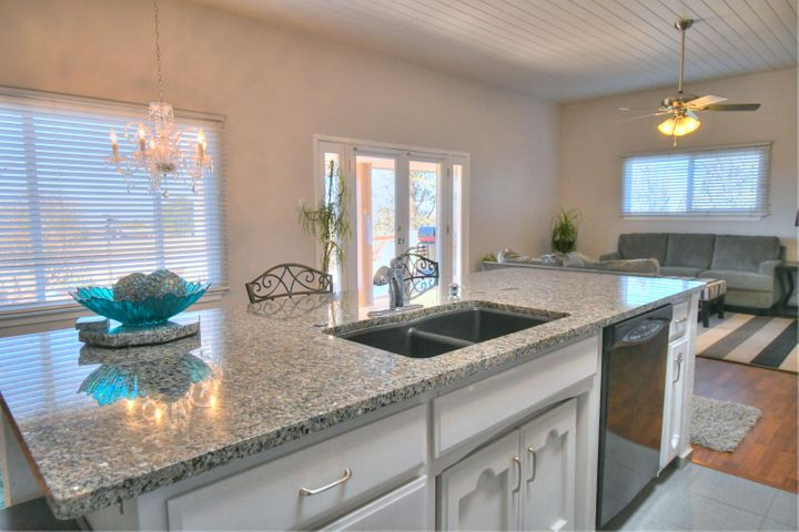 Wow! Open, light and bright! Gorgeous Sandia Heights home! Walk in to a private courtyard & expect to be delighted! Dazzling great room filled with light by the day & views of the sunsets & city lights by night.Re-modeled kitchen offers a gorgeous, HUGE island that defines taste & style. The greatroom has a cozy kiva fireplace and high ceilings that are painted wood for a clean look. Wonderful, very large flex room that looks onto the charming courtyard can be a media room, family room or a 3rd bedroom. The owner's suite also has patio doors to the courtyard & has a large walk in closet and an updated bath.The second bedroom has an en-suite& has a large walk in closet. Pristine yards with wonderful views! SUNSETS! CITY LIGHTS! New HVAC system! Lower property taxes! Oversized garage!