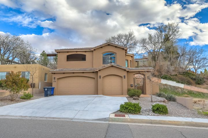 This Tuscan style home is a rare find in the heart of Albuquerque. Built in 2014 this home has all the best features including beautiful wood and tile floors inviting you into the open living space. Gas fireplace, raised ceilings, 3 car garage, large bar and island in the kitchen with granite counters, SS appliances and pantry. Master Suite is downstairs with it's own private laundry area. Upstairs has 3 more rooms, additional loft area with private balcony and views of the Sandias. This home is a short distance to parks, UNM, hospitals and more. Close to freeway access and downtown. Low maintenance landscaping. No PID or HOA. Schedule a showing today.