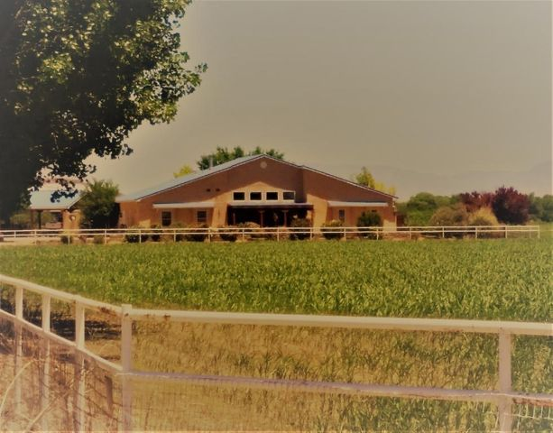 Living is easy in this stunning 5085 square foot southwestern home on private 2 acres with 1200 square foot open floor plan guest house. The house sits on 2 acres, Tract A, and the farm is on 36.18 acres Tract B. The farm parcel number is 1010031170345000000 and is leased land. The spacious main residence includes 3 bedrooms, 2 full baths, 3/4 bath and 1/2 bath. Both full baths have large jetted tubs for your relaxation and enjoyment.  Generous living space with 2 living areas, gourmet kitchen with GE appliances and Swanstone countertops. Highlights include hand carved woodwork and cabinetry through out the home. Entertain in grand style, large wet bar, oak floors in all the main rooms and 14-foot ceilings with wooden vigas. Every detail was carefully selected and quality crafted.