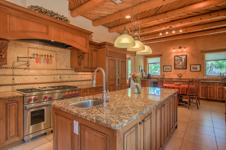 Unique opportunity; A historic mission style adobe home renovated with every modern luxury, kitchen has all Wolf appliances, Subzero, radiant heat, 2 HVACS, a new TPO roof. All within a warm and natural setting created by adobe walls, vigas, latilla ceilings, stone, tile, and all exterior adobe walls. Featuring an open floor plan: dining room, sitting, living, and family room open up to an interior courtyard. Two master suites with oversized bedrooms. Office or gym included. Huge master suite opening up to the inside courtyard complete the rest of this home. Bordered by large trees, a park sized yard, 1.5 irrigated acres.  Backs up to an equestrian and pedestrian trail. Beauty, serenity and opportunity to have anything from horses, a farm, or soccer field. Come define this magic property