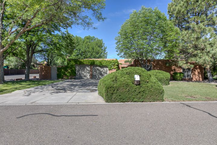 A wonderful near-north valley find. Large park-like lot with two covered outdoor living spaces, lots of grass and trees.  Lush yard is on an irrigation well--no high water bills. Close to the Bosque and ditch for walking. Old Town, museums, and restaurants close by for entertainment.  Southwestern flavor with two Kiva fireplaces, beams, and courtyard entry. This house has it all.  Master suite has a large bath, Kiva, and backyard access. The other three bedrooms are spacious and well situated.  One could double as a study/guest room. The large family room opens into the remodeled kitchen as well as to outdoor spaces.  The kitchen has granite, stainless and a great stove.  The large windows in the living room show off the backyard fountain, planting beds and paths. A visit will sell you.