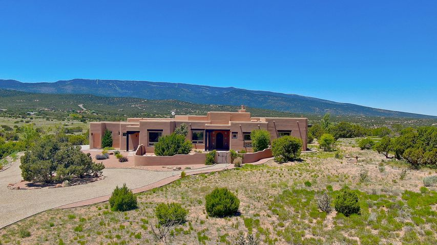Gorgeous Custom Home in Sandia Park! This 2014 Built One Story Home by Casa Bella sits on 10 Acres with beautiful views of the Sandias! This Light and Bright and Impeccably Maintained Home features 2X6 Construction, Radiant Floor Heat with 8 Zones, REF AIR, Natural Gas was just plumbed in October '18, Security System,  2 Master Suites and Two BR's with Jack and Jill Bath! The Family room has 14'  Beam Ceilings, KIVA FP and a Pocket Sliding Door that opens to the Portal. The Master Bedroom w/Beam Ceilings & Pocket Sliding Door to it's private Portal!  The amazing Gourmet Kitchen has the Monogram Series appliances complete with a 48'' 6 burner cooktop, 48'' built in SS Ref,  large kitchen Island with beautiful granite and a large kitchen nook.  Custom office by California Closets! MORE
