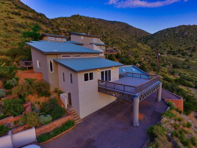 Contemporary living, modern elegance,  & tranquility await you high up on the hill! An artistic and open floorplan. Offering unobstructed views as far as the eye can see! Sunset views of Mount Taylor adorn the evening sky.  Surrounded by  open space to the east & south and direct access to walking trails.. This unique custom split level home is a certified wildlife habitat and frequently enjoys visits from a wide variety of animals. The complete remodel brings modern color and  flair to this  amazing dream home!