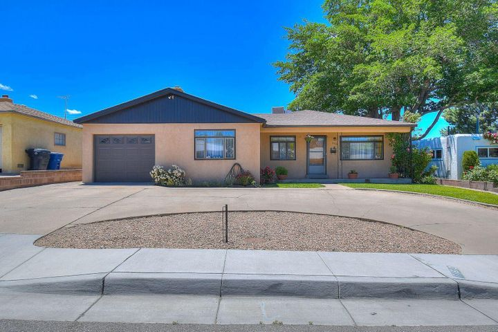 Located in the Northeast Heights, this home has been well maintained and features a unique drive thru garage, open and covered back patio, remodeled bathrooms, and a large lush backyard. Come home and enjoy the views of the Sandia Mountains from the covered patio in the front. This will not last long! Scheduling a showing today!