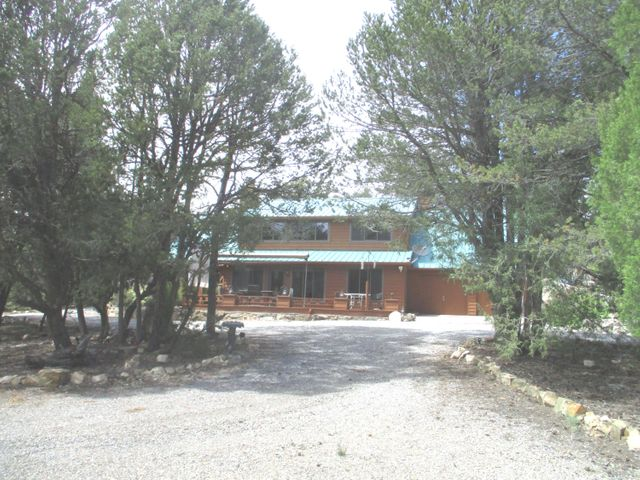 This is a uniquely lovely home (all electric) in an incomparably beautiful setting surrounded by Cibola National Forest. Sunny entryway and newer Anderson windows bring the forest and the sunlight into your living area which is graced by T&G soaring floor-through ceiling, T&G fireplace surrounding and custom built in bookcases.  Kitchen and dining nook have great forest views.  Master on first floor with custom fireplace.  Half bath on first floor for guest use.  Upper floor has 3 bedrooms plus bonus room with access to the outdoors plus a full bath. Outdoors find huge mature trees, a five-hole green, driving cage and sand trap.  Solar powered gate, water harvesting system with drip tubes to shrubs and plants, native rock pond with waterfall, brick floored gazebo.  Paved road access.