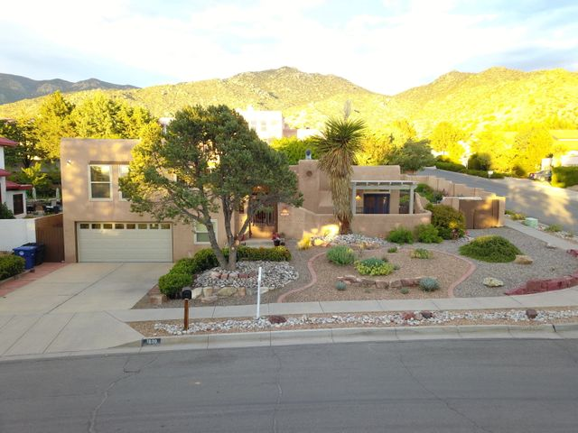 COME TAKE A LOOK  Great PRICE reduction for this beautiful home in the foothills.   Seller ready to move to her new  home and wants  this sold.  Custom pueblo with 3/2 ,custom touches with latiilas, tongue and groove ceilings, nichos and bancos .  Backyard is gardening oasis,  with trees, shrubs, roses, lawn and gazebo.  Green house and hot tub .  Covered patios,  french doors open to pergola and perfect sitting area.  Refrigerated air,  new wood floors, master suite with a large sitting room/office/ nursery and walk in closets.  This home has been beautifully maintained.   Seller has moved most of furnishings.  Minutes to KAFB Sandia Labs  Great walking trails