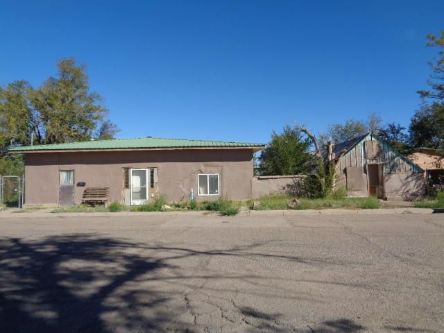 Adobe house with tons of potential. Exposed vigas in a couple rooms. Owner installed thermal windows and upgraded the electrical a couple yearsago. There is a front living room and den in the center of the home. It has 3 bedrooms without closets and 1 1/2 bathrooms. There is a large laundry room. Large covered patio and fenced yard. The detached structure next to the home is not salvageable.