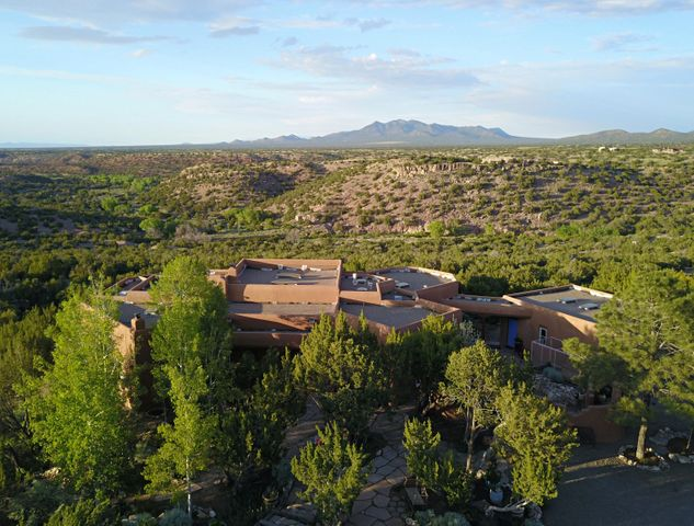 An Exceptional SW Residence Embracing Unparalleled View of Mountains, San Pedro Creek Open Space, Santa Fe and Beyond. Bordering the San Pedro Creek Open Space, this Property is Sophisticated with many Artisan Touches. Upon Entering the Dramatic Hand Crafted Door you will immediately feel reminiscent of Old Mexico and Santa Fe. Lovely Flagstone and Wood Floors, Beamed Ceilings, Nichos, Kiva Fireplaces, Fabulous Portal and Courtyard with Gorgeous Gardens. Architectural Open Floor Plan With 2 Large Bedrooms and Huge Office. Property has a Box Car for 320 sq. ft. of Storage or Future Guest House? You Can Walk to the Creek and Access Many of the San Pedro Creek Trails From this Property. Private Electric Gate.