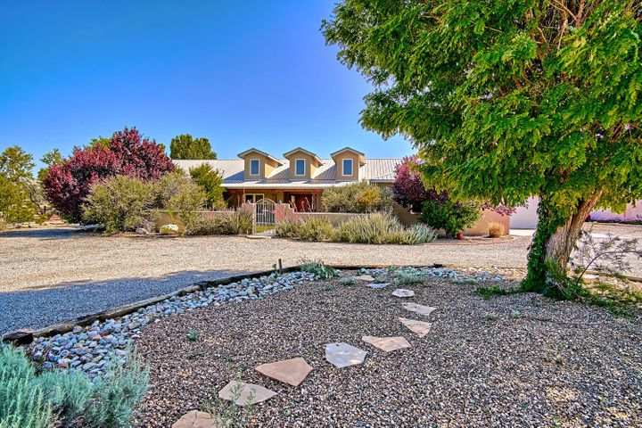 Lovely Northern New Mexico style home with soaring cathedral ceilings & dormer windows.  Entertain your guests in the great room with a kiva fireplace and wet bar.  The culinary expert will relish the kitchen's large island with prep sink, granite counter tops, stainless steel appliances, custom cabinetry & pantry.  Breakfast nook overlooks patio area.  The large dining area is currently used as a family room.  Enjoy the serenity of the back patio with a bubbling water feature & lush landscape.  Take the chill off those winter nights with a roaring fire in the master bedrooms's kiva fireplace & soak in the jetted tub. 18'' tile throughout except for carpeted bedrooms.  Radiant floor heat & refrigerated AC.  Even your vehicles & toys will be happy in the 4-car garage.