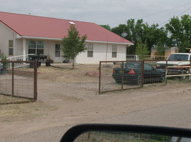 Nice home, but seller is currently in process of cleaning & removing much from the exterior of the property. Interior of the home is clean and has been maintained, the grounds around the home have been used for horses, chickens, etc., so needs a clean up. Garage is an older adobe structure, but very serviceable. Home has a heat pump/cooling system only 2 years of age, there is a propane heat stove in the living room that the current owner has never used as it was not functional when she purchased the home & it is no longer needed. Seller will do a carpet allowance with an acceptable offer. Property can be irrigated thru MRGCD. 3.09 acres to use as one wishes. All portable panels & chicken coops do not convey with the property.