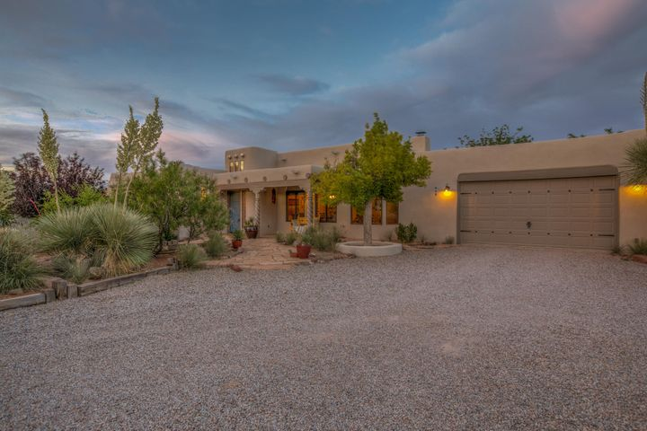 Corrales at its finest! One story easy southwest living. Situated on .8 acres, this lovely home has been meticulously maintained with updates galore!Newer stucco, roof, Kitchen remodel with hickory cabinets, granite, and fabulous backsplash. Living room boasts a lovely Kiva fireplace Vigas and Latillas in on the ceiling,  stunning Saltillo tile floors. Bathroom updates include vanities, tile work and more! All this and you won't want to stay inside, the grounds of this property are lovely.  A private rear garden features a covered patio with city and mountain views, a private seating area outside the master bedroom, grass, flowers, trees, a fountain. You really have to see this to appreciate the beauty. This is sure to sell quick, don't miss out!