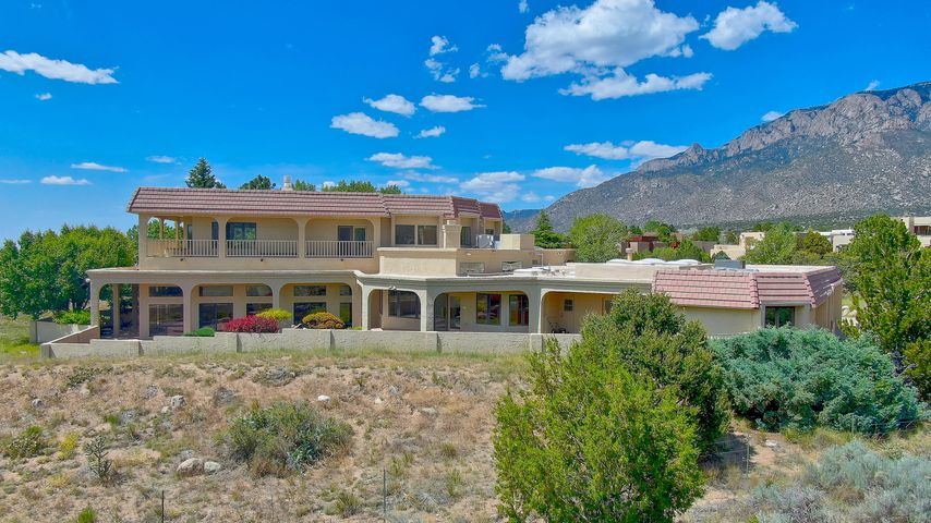 Estate Sale- Now Priced at 2019 Appraisal!  BEST BONES!!  Original, one owner classic Territorial custom home by Hacker. Outstanding private culdesac lot with gargantuan vistas from the Rio Grande Valley to the Sandias! Indoor heated & cooled pool room is well separated & closed from the functional floorplan. The master ste inclds office/ workout/ nursery, his & hers bath, huge walk-in closets, gaslog frplce & private covered balcony with absolutely forever 360 views. Separate family room designed with two bedrooms & jack-n-jill bath- for the growing household.  Multiple living & dining areas, chef's kitchen with island, nook, huge pantry & more great views/light.  Great bones, tons of space & livability- this is a huge opportunity! Get there now and see for yourself. Motivated Sellers!
