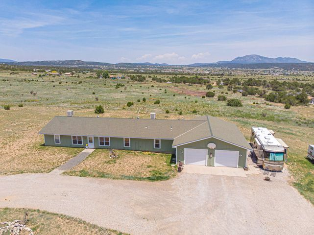 Custom ranch style home on 5 acres has  360 views of the mountains & valley!  This home was designed & built with attention to detail, has steel framing & a garage that can fit 4+ vehicles, workshop area, attic storage & is heated!  Kitchen has an island with bar, lots of counter space, huge pantry, Pergo flooring & is open to the family room. Master suite has an attached flex space that could be a hobby room, office or sitting area, 2 walk in closets & master bath with jetted tub. All bedrooms have walk in closets. Jack & Jill bath for 2 bedrooms.  FRESHLY PAINTED, vaulted ceilings, plant ledges, ceiling fans, 2 evap coolers, radiant heat throughout, RV hook-ups, partially fenced, horses are allowed. Roof will be replaced (up to $15,000)w/ acceptable offer.  Buyer can pick shingle color.