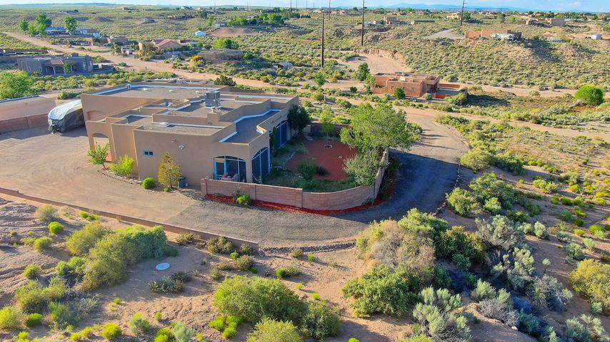 Enjoy beautiful East Sandia views from the screened patio on this 1 acre, 4 bdrm, 2 bath, Southwest-style hilltop home. Studio 598sq.ft.+- w/mini-split not included in heated 2157sq.ft. Parking w/3-car garage & separate tandem 2-car Studio garage & dedicated driveway. Small Office links studio w/ main garage & laundry rm entrance to home. Split floorplan, separated by living area with barn door for 2-bedroom privacy. Barreled ceilings in entry, hall, & MB entry. Refrigerated AC (2017) & both forced air & radiant for heating. Office/4th bdrm has ceramic tile (2017)& separate entry. Pergo laminate flooring, new pipeline from well to house, water softener & new water pump, sola-tubes-- studio, & retaining wall along driveway. Gas & electric for stove & dryer.     Your sanctuary in the desert