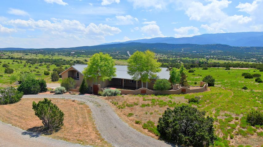 Extraordinary custom Crombie home, on 10 incredible acres! Fantastic panoramic views, ski slopes, Santa Fe lights, and surrounded by five mountain ranges. Open floor plan w/ raised ceilings and large Pella windows to see all the views. Wonderful kitchen with tons of cabinet and counter space, 2 living areas, master suite with beautiful master bath, spacious bedrooms, office with built-in desk & cabinets, 2 closets, and could be a 4th bedroom. Fantastic upstairs game room with bar, cabinets, wine cooler, built-ins great for entertaining. Inviting courtyard and splendid backyard with covered patio perfect for enjoying the summer mornings and evenings!