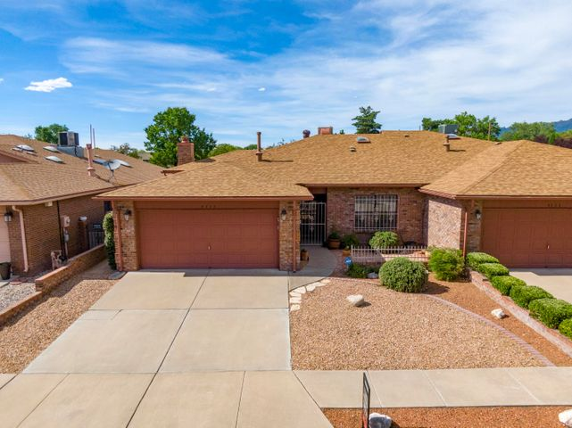 Wonderful NE Heights home! Great Northeast location near ABQ Academy and Tanoan! No HOA!!! This ALL Brick, 1 story townhome offers 2 bedrooms, possible 3, 2 baths, and a 2 car garage. Grand living room with wet bar, 2 dining areas,  raised/vaulted ceilings, & ceiling fans. Lots of natural light! Kitchen has stainless steel appliances and 18 inch tile. Huge master bedroom with office (or option for 3rd bedroom), master bath with over-sized shower and double sink vanity. Two year old roof with warranty! Tons of storage, low maintenance back yard with patio and great views of the Sandia Mountains. Home is in immaculate condition in a very quiet neighborhood.