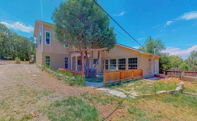 Rare opportunity in the highly desired historic Village of El Cedro. Turn key, open concept floor plan with 2 living areas, kid's room with loft or multi-functional room. Potential for a 3rd or 4th bedroom. Upgrades include newer septic system & leach field in 2016, recent stucco, windows & carpet on the upper level only, tile in kitchen, & fresh paint throughout. New shingle roof will be complete in July. Nestled on a 1.37 wooded acre lot that extends to Highway 337. Come relax & breathe in the fresh mountain air from the private balcony that overlooks this secluded getaway. Two bonus cabins for work, play or to create your own unique space. Both will be fitted w/new corrugated metal roofs in July. Convenient location, approx. 20 minutes from the Big I interchange, near camping