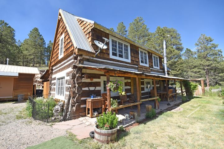 It's hard to beat the charm of this historic log cabin that was one of the originals in Vallecitos! Built in the 1920's, this hand-hewn log home has many upgrades but still has an authentic, rustic ambience.The traditional open concept cabin floorplan includes a country kitchen on the main level with updated appliances & an antique cookstove.The cozy living room with wood burning stove is the perfect place to relax. Farmhouse bathroom with claw foot tub.Bedrooms are on the second level and  the updated windows bring in plenty of light.Outside you will find  outbuildings with just as much charm.Workshop with plenty of room for all of your projects & toys,  an exercise room & chicken pen. Wood shed & large Pole Barn. It doesn't get much better than this, schedule your showing today!