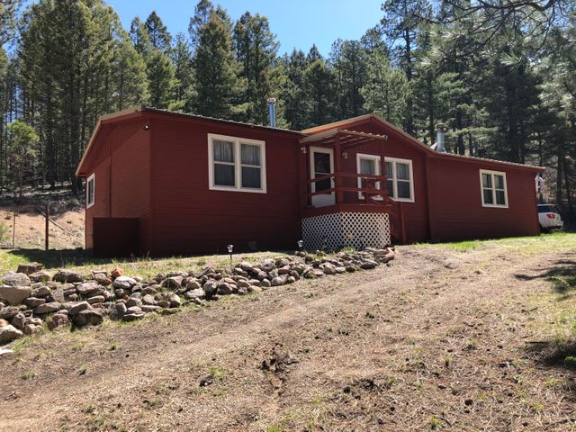 Get ample square footage and acreage with this 1600+ sq.ft. home on almost 2 1/2 acres in the Sierra Los Pinos subdivision of the serene Jemez Mountains. Three bedrooms, two bathrooms, well-maintained interior, with both a pellet and wood-burning stove. Multiple cosmetic updates inside and out including fresh paint on the exterior of the home, brand new front porch and steps in back. This property also boasts a large garage/work shop for storing all the equipment, toys, and tools you need to enjoy your new mountain home. Located approximately 45 minutes from both Los Alamos and US 550 with dining, entertainment, shopping, and outdoor recreational outlets in each direction including the Valles Caldera National Preserve. Home is sold as is with no warranties express or implied.