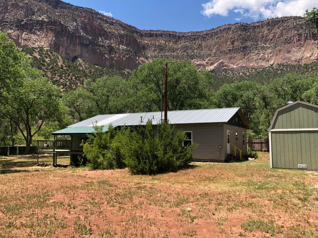 PRICE SLASHED. Over 2 acres spanning both sides of the Jemez River in this dreamy park-like setting with bosque cottonwoods! Large covered, wraparound porch for shade, picnics and relaxing.  Huge fenced yard for kids, dogs, or rowdy adults! Fabulous high-end flooring throughout!  New electrical upgrades including backup generator! New windows! Three split heat/air conditioning units. Super security system!   Oversized insulated 2 car garage and the riding lawn mower stays.  Get it now before it's gone!