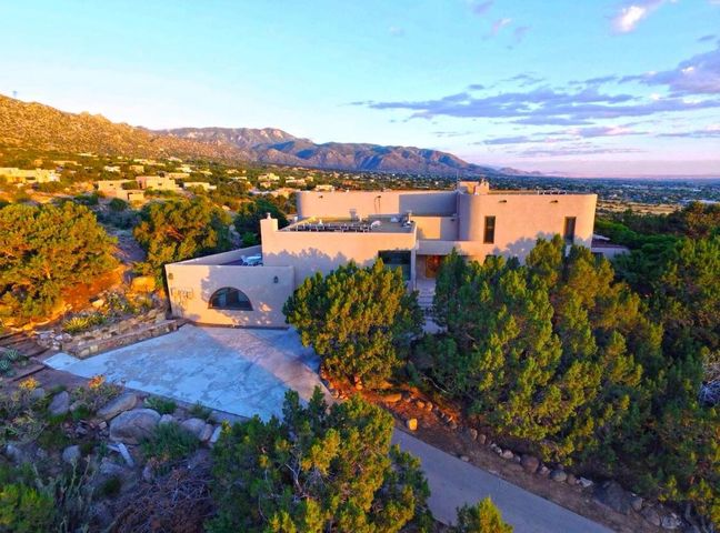 Custom Home in a Private Setting with breath taking panoramic views. Located in Sandia Heights. Possible 4 bedroom with an office! One owner, Open floor plan with ceiling to floor windows bringing in tons of natural light & endless views!  Relax year round in the indoor pool and spa! Spacious family room overlooking the pool, with a patio to see the incredible city views.Large master suite with jacuzzi jetted tub, with an exit to a private deck.Don't forget about the first level In-Law Quarters with a Kitchenette & Wood burning stove.  Photovoltaic solar, pool solar, domestic hot water solar, & passive solar. Electric bill only $8 a month.Ton's of outdoor living space to enjoy the surrounding nature. Plenty of space to add convert rooms & make it your own.A perfect place to call home!