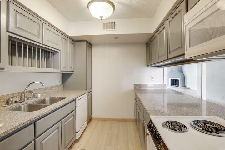 This unit has fresh paint, new carpet in 2 bedrooms, 3rd bedroom is tiled and can be a 2nd living area or office (closet in 3rd has been removed - owner used as office).  Living room with cozy fireplace and tile floor, dining area, kitchen with built-in microwave. This is complex has with easy access to I-25 in a community with gated entry and security, assigned parking, swimming pool,  fitness room, children's play area and club house.  HOA dues covers gas, water, trash++
