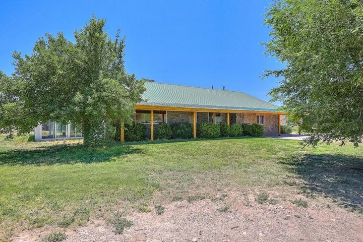 Nice custom ranch style house.  3 bedrooms, 2 baths, Propanel roof, refrigerated air,  radiant heat. Beautiful rural area, 2.69 acres perfect for small horse set up, mountain views and in the heart of the Los Chavez green belt. Property is irrigated with ditch waters rights and has 2'' house well. Large 30'x50' shop well built with a 10'x20' office/apartment with full bath and 50 gallon water heater. 2 car garage/workshop 20'X30' with 8'X10' storage sits along side additional 24'X24' stucco shop, insulated & wired for 220. Behind the saddle house is 1080 sq ft RV cover or could be used for hay storage.  The 12'x 24' insulated saddle house sits adjacent to the 120'X 300' pipe fence area can be used for arena and/or more pasture. Just 20 minutes from ABQ Airport and 10 minutes from either th