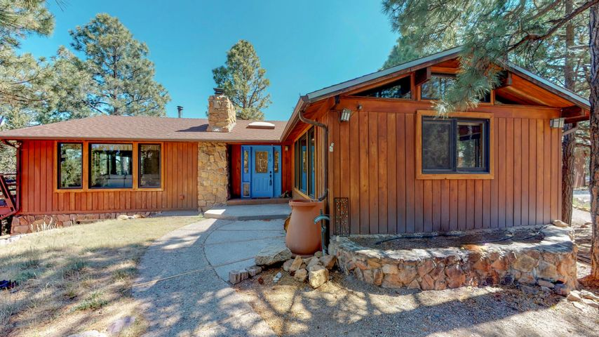 Your Private East Mountain Retreat Awaits! Picturesque Sandia Park home nestled among the Ponderosa Pines along the Crest Highway.  Large viewing windows and wrap-around deck bring the beautiful forest indoors. Open flowing floorplan with updated kitchen cabinets, countertops and Kitchen-Aid appliances + wine fridge.  Newer carpet and updated bathrooms marry with the charming stone fireplace, warm solid wood walls and cozy wood burning fireplace.  Spacious downstairs walks out to the deck and grassy back yard, and includes a 3rd and possible 4th bedroom and workshop area.  Perfect for multi-generational living or vacation rental!  Awesome oversized drive-thru garage, and fully fenced and gated.  Just minutes to Forest trails, skiing, shops, restaurants and Albuquerque!
