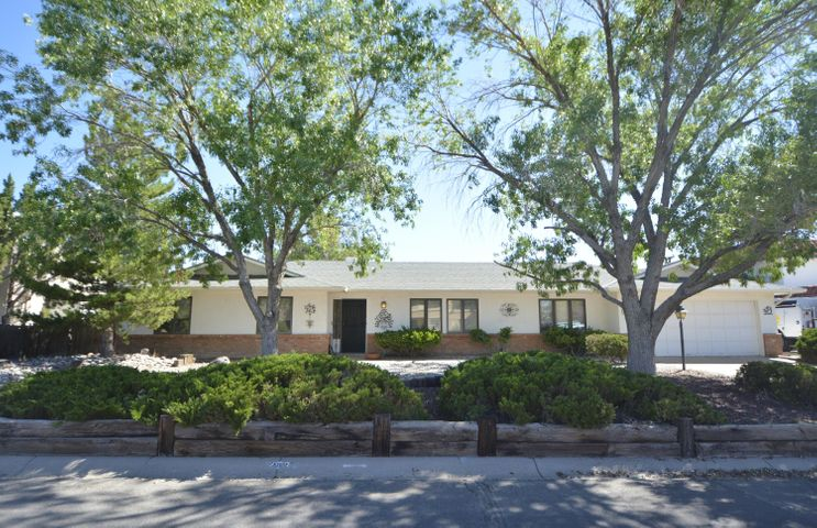 One story 3BDR/3BA/2CG on approx 1/4 acre lot in the heart of Rio Rancho!  Refrigerated Air!  Beautiful wood windows throughout!  TWO living areas!  Huge living room & formal dining room with plenty of room to entertain!  Family room featuring a brick wood burning fireplace and sliding doors to the outdoor covered patio.  Kitchen has beautiful cabinetry in excellent condition, two pantries, a large breakfast bar and breakfast nook.  Master suite features an updated bath with raised vanity, soft close drawers, large shower & tile flooring.  Oversized backyard with mature trees and shrubs, covered patio, perfect for summer BBQs and relaxing and enjoying the best of NM weather!  Close to parks, schools, library, shopping, Intel and Presbyterian Rust Hospital!