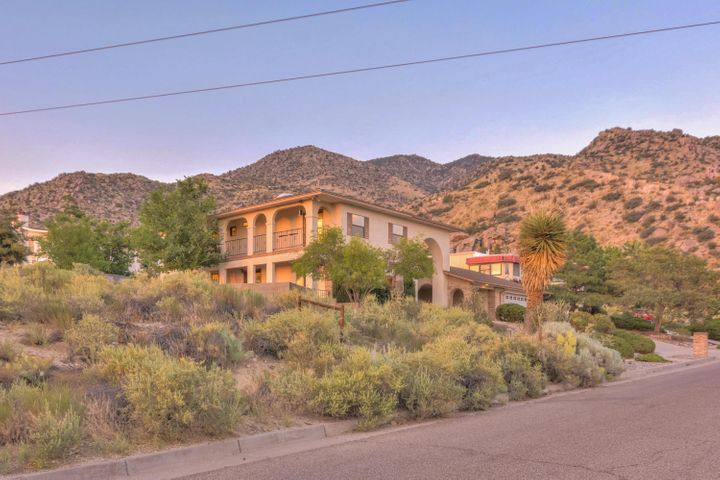 Move-in ready luxury in prime Sandia foothills. Priced below market--just add finishing touches. 2 levels/3BD/3BA. Sweeping balconies, patios. Foyer w/open stair. Formal LR, DR. Tile, wood, carpet in BRs. French doors. Storage! Kitchen open to breakfast room, counter bar, new SS appl. FR w/soaring ceiling. Main floor laundry, bath, wine cellar, attached 2CG, carport. MBR w/French door opening onto balcony w/mountain views. WIC and wall closets. En suite bath w/custom tile, built-in niches. Jetted tub, step-in shower, large vanity w/make-up station. Water closet. Two add'l BRs, one w/balcony access, hall bath. Oversize lot. SW pro landscape w/stone walls, flagstone paths, block privacy wall, back yard access. Brick/stucco ext., thermal double pane windows, skylights, 2+ evap. cool units.