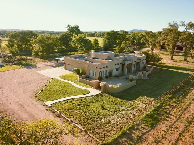 This fully custom southwest home and horse breeding facility is situated on 10.65 acres. The home is top of the line, with a fabulous Chef's kitchen, granite counter tops, custom cabinets, Wolf brand dual fuel 48'' slide in stove, Wolf built-in warming oven, a built in KitchenAid microwave and refrigerator. Walls are diamond plastered, accented by solid alder-wood doors, travertine floors, as well as vigas. Also featured are nichos, Pella wood sliders and wood casement windows with built-in blinds throughout.  The Master Suite features a workout room, gas log fireplace, huge walk-in closet with separate cedar closet, an en-suite bath with his and hers vanity/dressing area, a massive walk-in 9-head shower and jetted tub. Also features a study with 3 walls of custom book cases! Come and see!