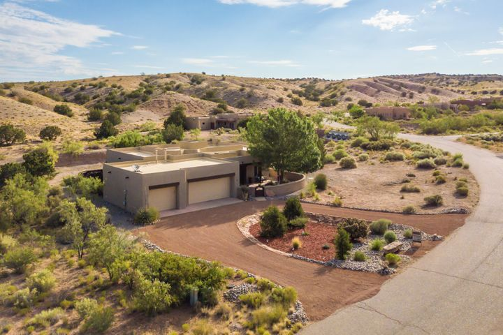 This beautiful single level Southwestern home is located in Placitas' Sundance Mesa subdivision, and is only 3.9 miles to I25! The kitchen features granite counters, a breakfast bar, butcher block island, s/s appliances, walk-in pantry and is open to the breakfast nook/great room. The formal dining room features a sliding door which opens to the covered portal and beautifully landscaped entry courtyard. The split-master suite is spacious and features an en-suite bath with jetted tub, dual vanity, water closet and walk-in closet. TPO roof w/ transferrable warranty (2018). The home backs to over 5000 acres of BLM land, offering a multitude of outdoor activities and unobstructed views of rolling hills from the covered patio and walled backyard. Lots of storage and an oversized 3-car garage.