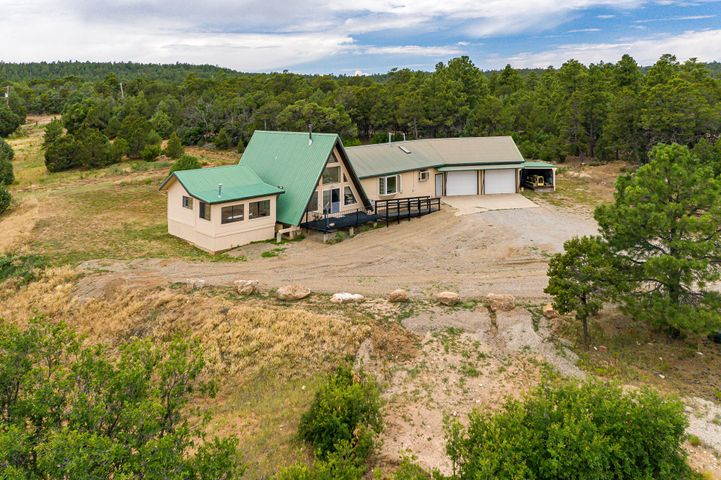 Mountain retreat on nearly 23 acres.  The property consists of 2 separately deeded parcels (12.2 & 10.3 acres) Main house, 1895 SF, heated 2372 SF shop, and barn.  The charming A frame style house offers great views, an oversize garage, hot tub room, country kitchen with wok stove !  The Shop offers endless possibility for auto enthusiast/carpenter, etc. features include: office with 3/4 bath, it's own septic system & propane tank, and  200 amp electric service.  The land is heavily wooded with ponderosa, pinon and old alligator juniper trees.  Additionally, there's some nice open/meadow areas, ideal for horses.   Situated towards the end of a dead-end road, this is ideal for those wanting a secluded retreat yet still within about 30 minutes of ABQ.