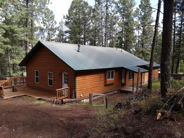 Enjoy the heavenly setting of the Jemez Mountains off of your wrap-around deck. This house has new luxury vinyl flooring, paint, light fixtures, septic system, furnace, and propane gas lines. It has 2x6 construction, vaulted ceilings, ceiling fans, and a huge 2 car-plus garage. There are two full baths. There are also new plex water lines. The exterior has been covered with log siding and boasts a metal roof. The inside has been paneled and updated for that mountain cabin/farm house look. It is on a community water system and the roads are cleared of snow in the winter. Enjoy this home year-round or perhaps a weekend retreat. It is so close to Albuquerque, Los Alamos, and Santa Fe. Outdoor recreation activities abound. Come on out and enjoy the beauty of this home and its natural setting.