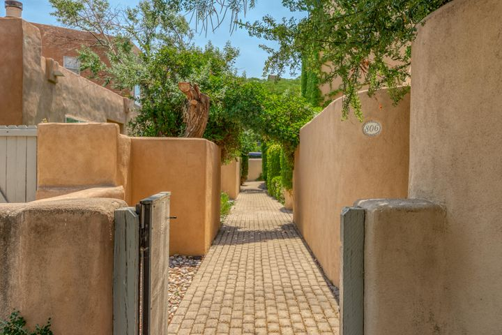 BACK ON MARKET!  Inspections are done.  Urban Living at its best!!  This home is like an oasis in the desert, with its lush courtyard entry.  Two sets of double doors grace the entrance.  When entering, you are greeted with soaring beamed ceilings, freshly painted plaster walls, original saltillo tile flooring, a wood burning fireplace with built in bancos, and so much more!  This unit was built by Roberson and own by acclaimed SW artist R. C. Gormon.  The charm here is never-ending!Hardwood flooring under carpet, built in sound system, refrigerated air, original brass hinges and door handles, lifetime warranty on roof material, 2 car garage, and close proximity to our vibrant Old Town and Sawmill District.  Close knit community with low HOA fees.  Authentic southwestern charm abounds!