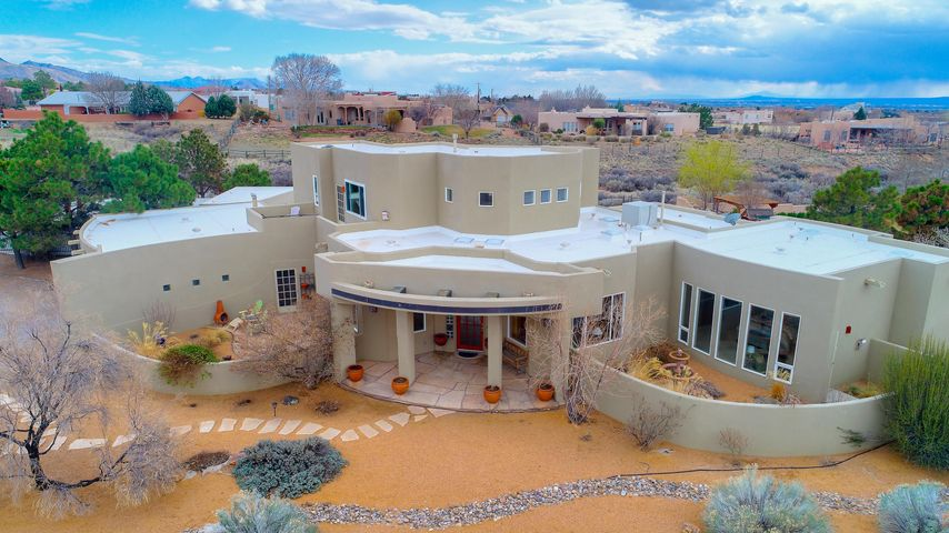 Outstanding 4-bedroom custom home in North Albuquerque Acres with views of the Sandias and an abundance of light throughout! Incredible floorplan includes huge main living area with soaring ceiling; gourmet kitchen with island, granite counters, BF nook, and stainless steel appliances; formal dining, office/study, radiant heat, family room/den with built-in entertainment center & bookshelves; 2 master suites: one on main floor with beautiful full master bath (double sinks, jetted tub, walk-in closet); other on upper floor with its own balcony, would be great as guest quarters. 319 sq ft stucco storage building and new TPO roof. Amazing entertainers' backyard with mountain and city views. 5-home Community/HOA amenities include: lighted tennis/b-ball courts, pool, park, and walking trail.