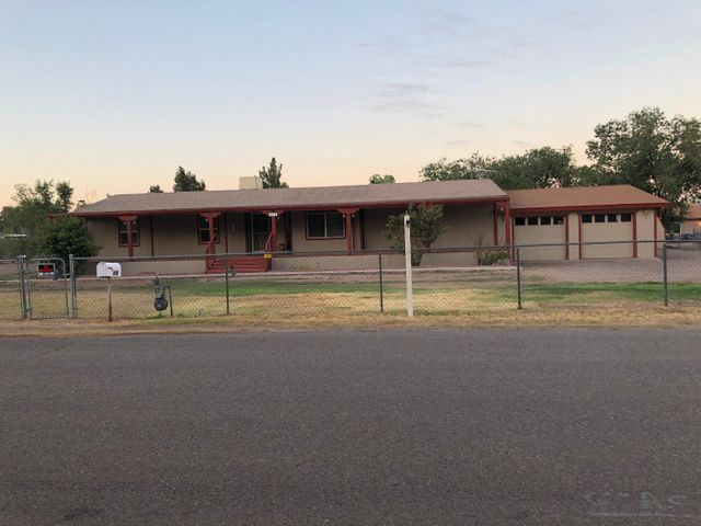 This .76 acre irrigated lot is a rare find just off of Edith and Montano. 2 car garage on a permanent foundation with another garage out back with access & a workshop on the side. Outbuildings for mowers and tillers etc. Over 2000 sq ft of living space on a Cul de sac next to the Acequia.