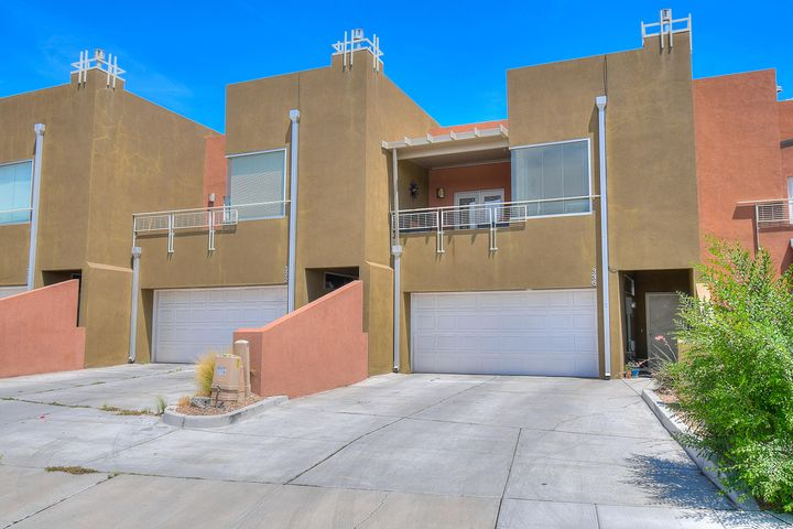 Gorgeous townhome with contemporary architecture, bright, open floorplan and  beautiful interior finishes. Great room, dining room, kitchen and master suite and laundry on main level. Bedroom & bonus room with closet on first floor. Custom gas log fireplace and carpet in great room. Balcony with views off of dining room. Kitchen has travertine tile, granite countertops with mosaic tile backsplash, breakfast bar, stainless steel appliances including refrigerator, built-in microwave, gas stove/oven & dishwasher, breakfast nook. Master suite offers laminate wood floor, ceiling fan, walk-in closet, double sinks, granite counters, jetted tub, separate shower, view deck. Bonus room could be 3rd bedroom. Walled backyard with southwest gravel, trees and covered patio. Walk to shopping in Nob Hill.