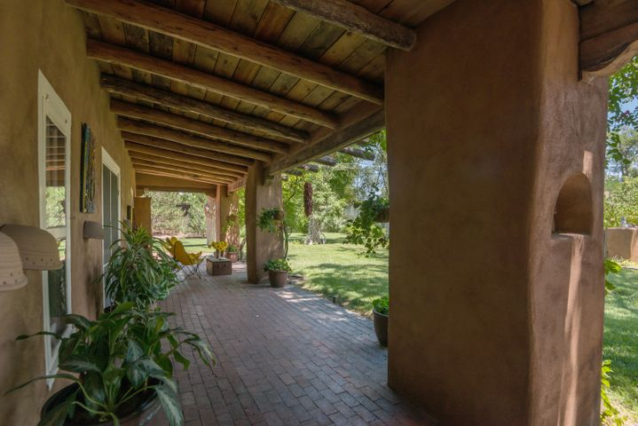 A rare opportunity to own this historic adobe 4 bedroom 4 bath compound in the heart of the Village of Corrales. Built circa 1850, lovingly renovated over time, these double thick adobe walls could tell many tales.Built in true hacienda style, the home is built around a central courtyard that provides light filled living spaces. A 4th bedroom is used as a private office. Towering cottonwood trees,lush landscaped yard provide private,shaded outdoor spaces. Next to trails for walking or riding, or stroll into Corrales for dining, this location is special. The property is also in the commercial zone, so the possibilities are endless. Small charming barn awaits your horses or toys. Authentic adobe homes have become rare in New Mexico, this one has the history,charm and ambiance of another era.