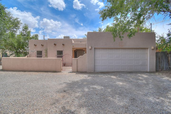 Pueblo style home located in older historic neighborhood just west of Rio Grande. Welcoming courtyard entry opens spacious great room floor plan with Kiva style FP & infused with natural light from expansive windows. Home is both light and bright. Large entry foyer. Oak cabinets, skylight and eating-bar in kitchen. Breakfast area off kitchen plus large dining room. Master bath has double sinks, separate shower and jetted-tub.Covered patio in private fenced backyard. Beams, skylights & nichos too!