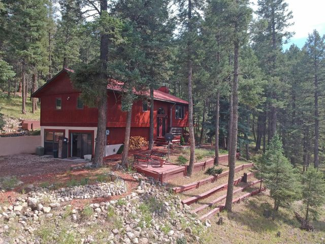 Life is good when you wake up every day to this stunning view AND have the Santa Fe National Forest as your extended backyard! Take it all in on the spacious deck of this well built, sturdy 4-bedroom, 2 bath home with a home office. Open concept living room & kitchen with plenty of counter space & cabinets. The garage has been closed in & made into a rec room, but could easily be converted back if you prefer. Situated on over 2 acres of thinned Ponderosa Pines, within the Sierra de los Pinos Subdivision, the delightfully landscaped property backs up to Santa Fe Natl. Forest and has an old abandoned logging road leading right into it just waiting for you & your outdoor adventures. Minimal road traffic makes it quiet and peaceful, but yet just a short 30-minute drive into Los Alamos.