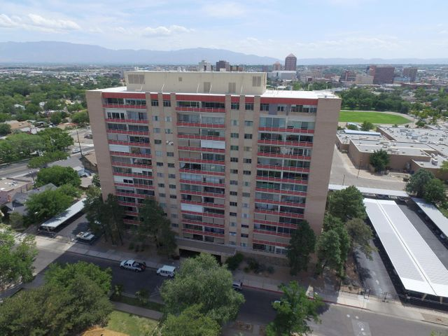 Here is your chance to own a quintessential piece of Albuquerque's history! This inviting, updated 1 bedroom unit on the third floor of Park Plaza boasts a full balcony for more spacious outdoor/indoor living overlooking the famous heart-shaped heated pool on the patio below.  Feast your eyes on spectacular city lights and gaze upon the majestic Sandia mountains every day from both the living room and bedroom.  Enjoy all the amenities of Park Plaza life from a full 24 hour gym to grilling on the outdoor patio. Secure access for both the building and the parking area. All utilities included in the monthly HOA fee, even basic cable! Recent improvements include acacia wood flooring, new kitchen appliances, and new vanity Come experience the luxury that only Park Plaza can provide!