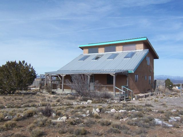 1590 SQ FT HOME ON 5 ACRES! $184,500. Level land! Fantastic views of the Sandias, plus Mt Taylor, Cabezon & the Jemez & Sangre de Cristo mountains! The property needs some TLC, as it has not been lived in for many years. No restrictions. Horses & other animals allowed! This 5 acres can be easily divided into two lots! 1 bedroom & full bath downstairs; 2 bedroom suite w/ bath upstairs! Open design with soaring ceilings & lots of exposed wood! Kitchen & great room have 16' tall ceilings! 3 car carport. 2 barns/storage buildings! This property is just 1,000 feet from thousands of acres of Public Land! Enjoy serene Sandia Mountain views from the 32x10 covered porch! Brand new water well is 520 feet deep! Bring your investors; property could also be subdivided into 5 lots! Being sold AS-IS.