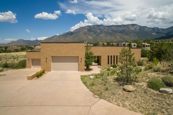 This dynamic contemporary home located in High Desert commands incredible views of the Sandia Mountains from both levels. Designed with clean contemporary finishes, and an open floorpan, this home was designed to provide a low maintenance lifestyle. Brick construction offers a unique design element combined with low maintenance. This home has so much to offer including a rare 5 bedrooms, a theater room, 2 living areas, an office or exercise room, 2 dining areas, and an oversized 4 car garage. Shaker style cherry cabinetry and doors are found throughout the entire home. The kitchen is an entertainers dream with a huge pantry, high end commercial grade stainless appliances, granite composite, an island & bar, and incredible mountain & city lights views. Hike & bike right outside your door!