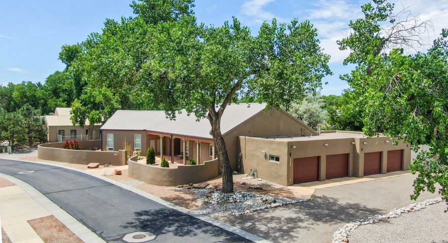 Desirable Old Town Gated Community of The Gardens, the only 4 Car Garage available! Custom Northern New Mexico style home is truly spectacular! Beautifully landscaped and on .33 acres it features RV parking/storage, 4 car garage, an inviting courtyard, along with open and covered patio's perfect for outdoor summer entertaining. Inside, this home offers a versatile floor plan w/ an elegant living room boasting high ceilings, a gas fireplace, and tons of natural light, plus a formal dining area, 2 sizeable guest bedrooms w/ Jack and Jill bathroom, an additional sitting room equipped w/ dual arch entryways, and an office/4th bedroom with separate entrance to outside patio. Gourmet chef's kitchen has large center island, ample cabinetry, SS appliances walk-in pantry PLUS a butlers pantry