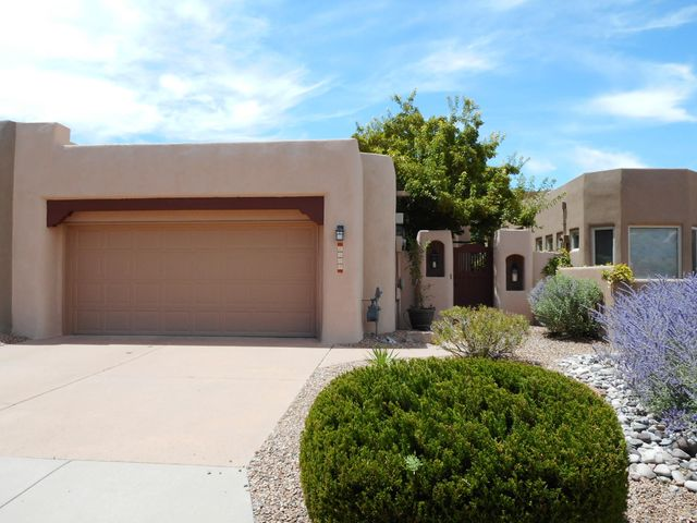 Here's that Pueblo Style Charmer you've been waiting for in the Popular High Desert Subdivision. Gracious courtyard entry! Freshly painted and carpeted with a new torch down roof!  Flooded with natural light! Bonus home office space in addition to the 2 bedrooms! Good sized Greatroom with built-ins and cozy gas-log fireplace and mountain vistas! Informal dining space. Functional kitchen with center island, pantry cabinet, built-in stove, cooktop, microwave, pull out cabinets, window seat and R/O system. Arched walls, security system, nichos and skylights! Generous Master suite with built out walk in closet and second full closet! Master bath features dual vanities, jacuzzi tub and separate shower! Easy care backyard with artificial turf. This great townhouse won't last long so see it today